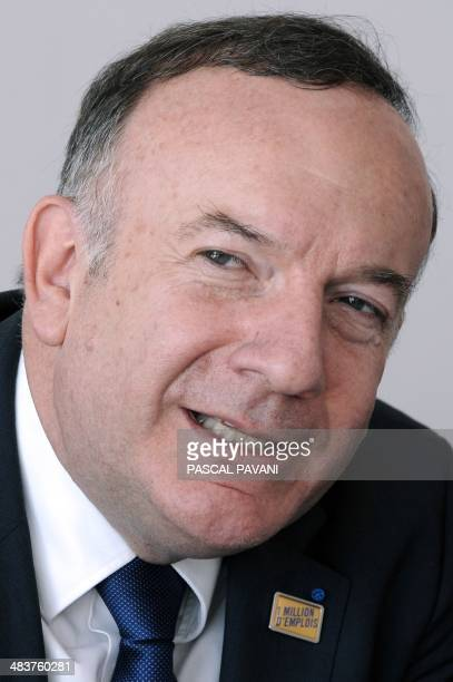 French employers association Medef's head Pierre Gattaz wearing a badge reading '1 million jobs' as aimed by Medef takes part in a debate during the...