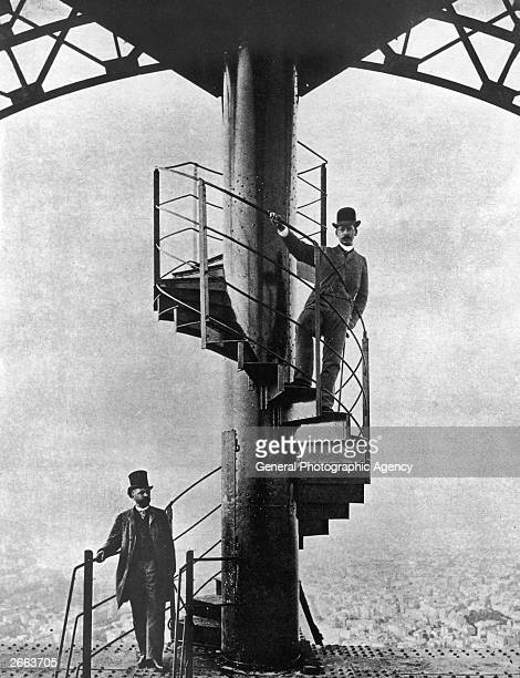 French engineer Alexandre Gustave Eiffel left poses high on the steps of the completed Eiffel Tower which he designed for the 1889 Paris Exposition