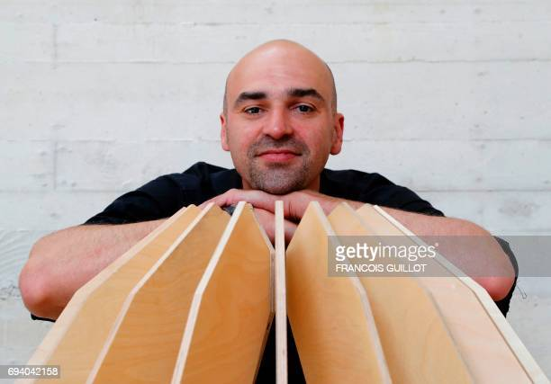 French engineer Arnaud Billard poses for a photograph as he sits amongst prototypes of furniture designed to filter out air pollution in Louveciennes...