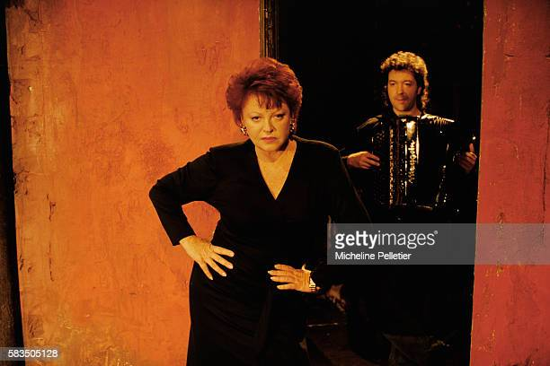 French entertainer Regine performing La boule au plafond at the Bouffes du Nord Theatre with an accordionist in 1993