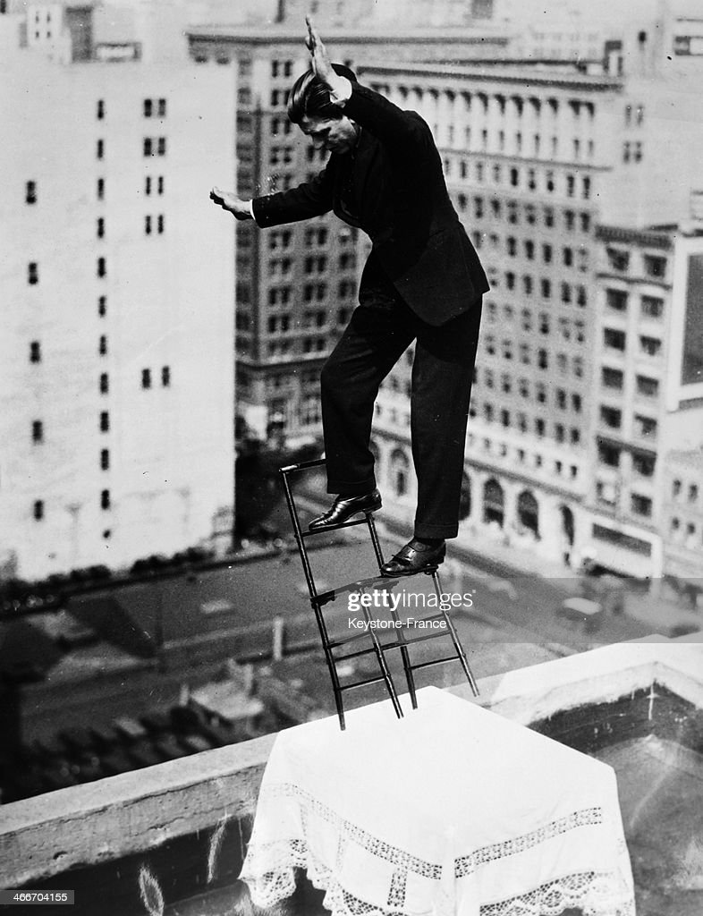 French equilibrist Gilbert Bettancourt tests his balance on a chair resting on a table with only two legs, close to the edge of the building roof on March 25, 1932 in New York City.