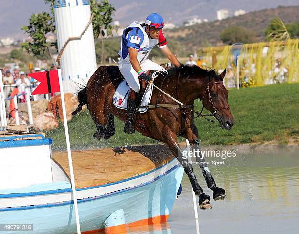 French eventing rider Jean Teulere and his horse 'Espoir de la Mare' jump a water obstacle 17 August 2004 at the Markopoulo Olympic Equestrian Centre...