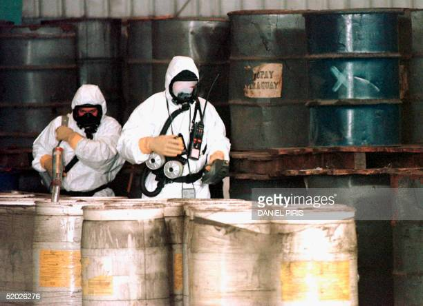 French experts in biological and chemical weapons check levels of radio activity as they inspect some 1118 metal filled with toxic waste in a storage...