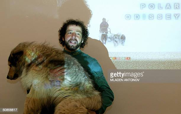 French explorer Gilles Elkaim shows to the journalists one of his polar dogs during a press conference in Moscow, 20 May 2004. For the first time in...