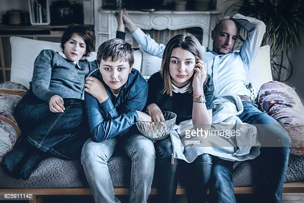 french family watching thrilling tv on sofa