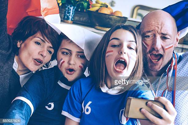french family with flag watching soccer game on mobile phone