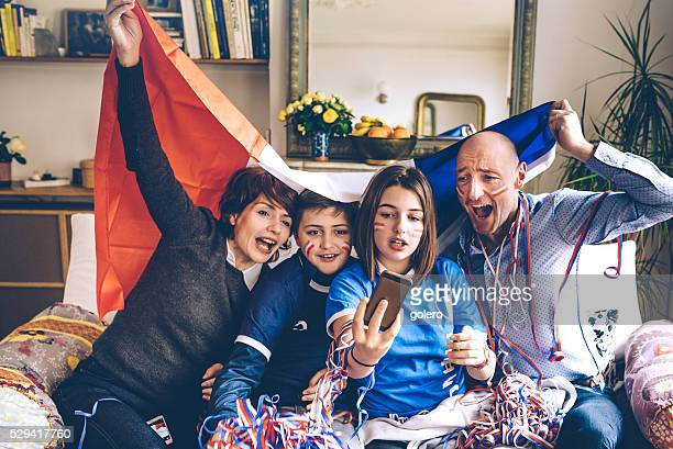 french family with flag watching soccer game on smartphone