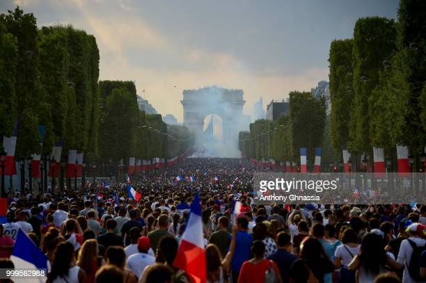French fans gather along the Champs Elysees to celebrate the France's victory over Croatia in the 2018 FIFA World Cup final on July 15 2018 in Paris...