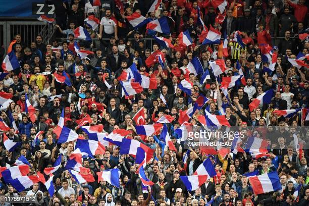 French fans wave French national flags as they cheer their team during the Euro 2020 Group H qualification football match between France and Turkey...