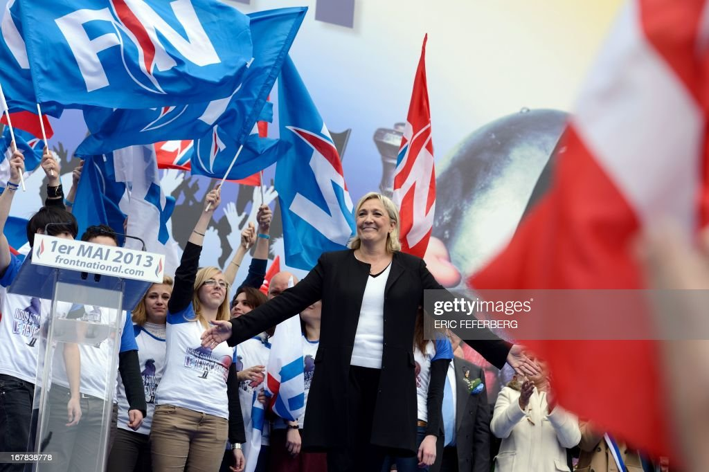 French far right Front National (FN) party president Marine Le Pen waves to the crowd after her speech, during the party's annual celebrations of Joan of Arc on May 1, 2013 at Paris' Opera square.