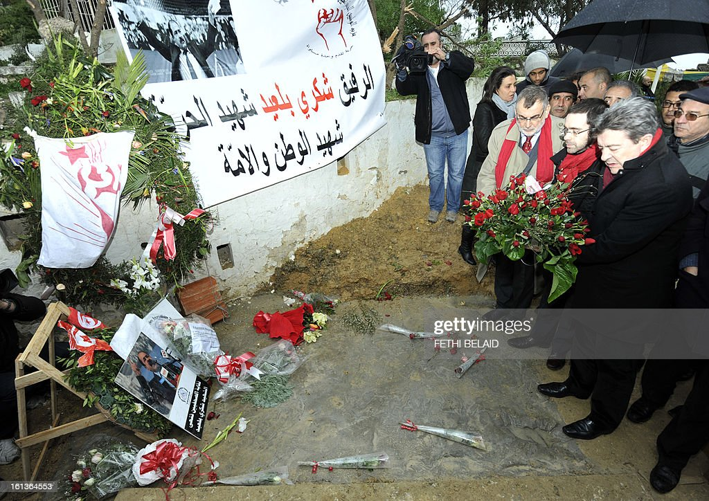 French far-left Parti de Gauche (PG) party leader, Jean-Luc Melenchon (R) readies to lay flowers at the grave of assassinated opposition leader Chokri Belaid in the el-Jellaz cemetery, on February 10, 2013, in the capital Tunis. Tunisian Prime Minister Hamadi Jebali's gamble on forming a new government in defiance of his own Islamist party after the assassination of Belaid has left Tunisia in political limbo.