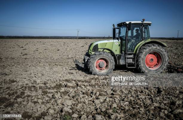 A French farmer drives his tractor to prepare the field for the culture of beetroot on March 24 in Bucheres near Troyes in the Aube department on the...