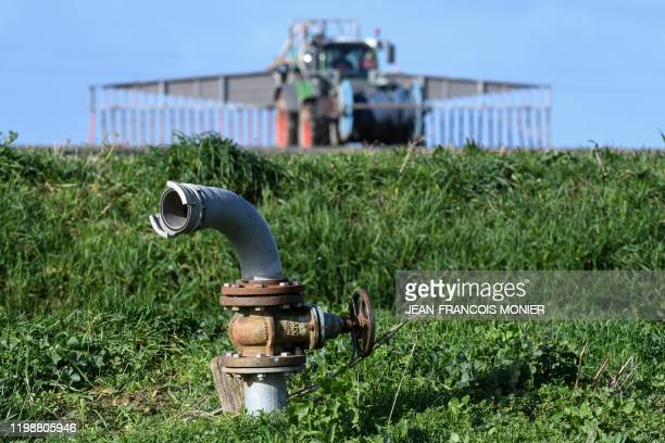 French farmer Nicolas Denieul spreads manure from his pig farming on the field, using a tractor linked to a buried pipeline, in Saint Germain Sur...