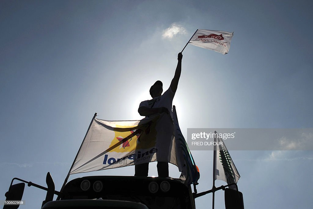 A French farmer standing an a tractor attends a demonstration in Paris on April 27, 2010 against wages cut and to denounce the European Farm Policy. The demonstration headed by grain farmers was called by 14 regional unions and backed by the National Farmers union (FNSEA).