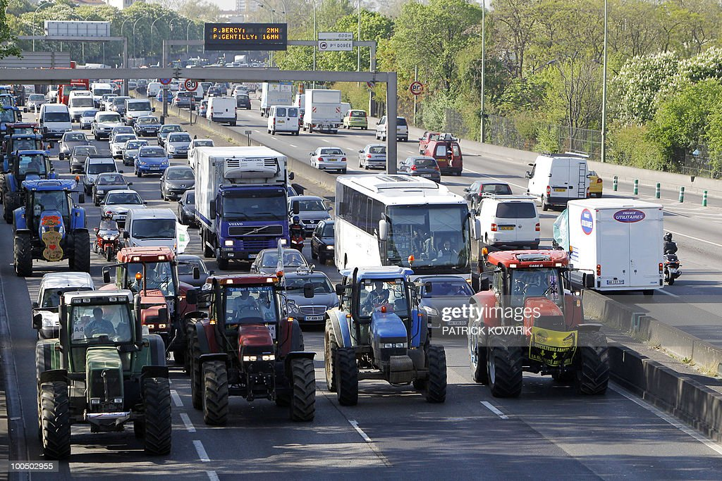 French farmers drive their tractors on Paris ring road, near the Porte de Vincennes area, on April 27, 2010 before demonstrating in Paris against wages cut and to denounce the European Farm Policy. The demonstration headed by grain farmers was called by 14 regional unions and backed by the National Farmers union (FNSEA).
