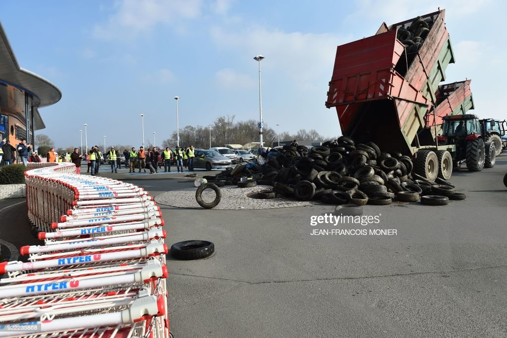 French farmers dump tyres onto a parking lot during a demonstration against France's signing of the EU/MERCOSUR agreements between Europe and South America, outside a super market on February 21, 2018, in Angers, northwestern France. /
