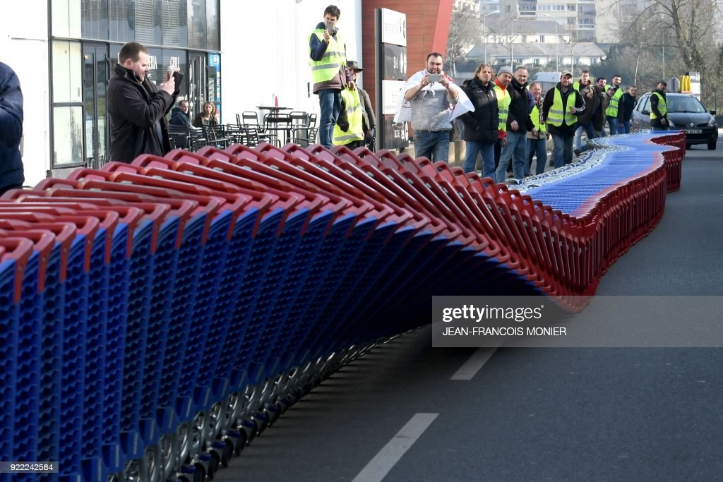 French farmers gather around shopping trolleys during a demonstration against France's signing of the EU/MERCOSUR agreements between Europe and South America, outside a super market on February 21, 2018, in Angers, northwestern France. / AFP PHOTO / Jean-Francois MONIER