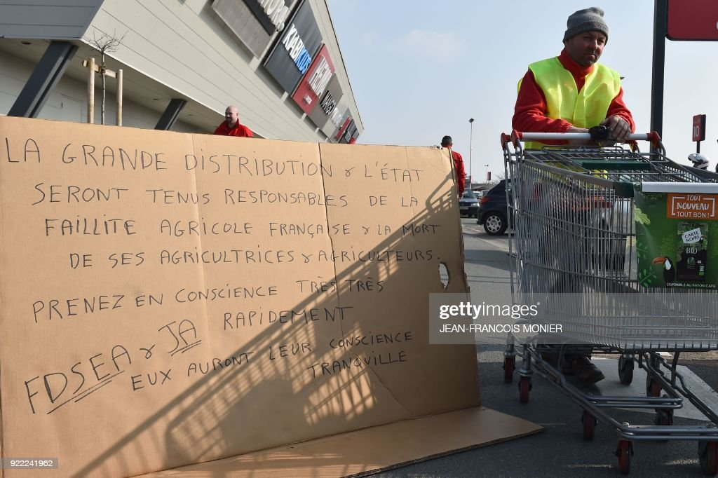 French farmers hold a sign that reads, 'The mass distribution will be held responsible for French agricultural bankruptcy and the death of its farmers. Take consciousness very quickly' during a demonstration against France's signing of the EU/MERCOSUR agreements between Europe and South America, outside a super market on February 21, 2018, in Angers, northwestern France. /