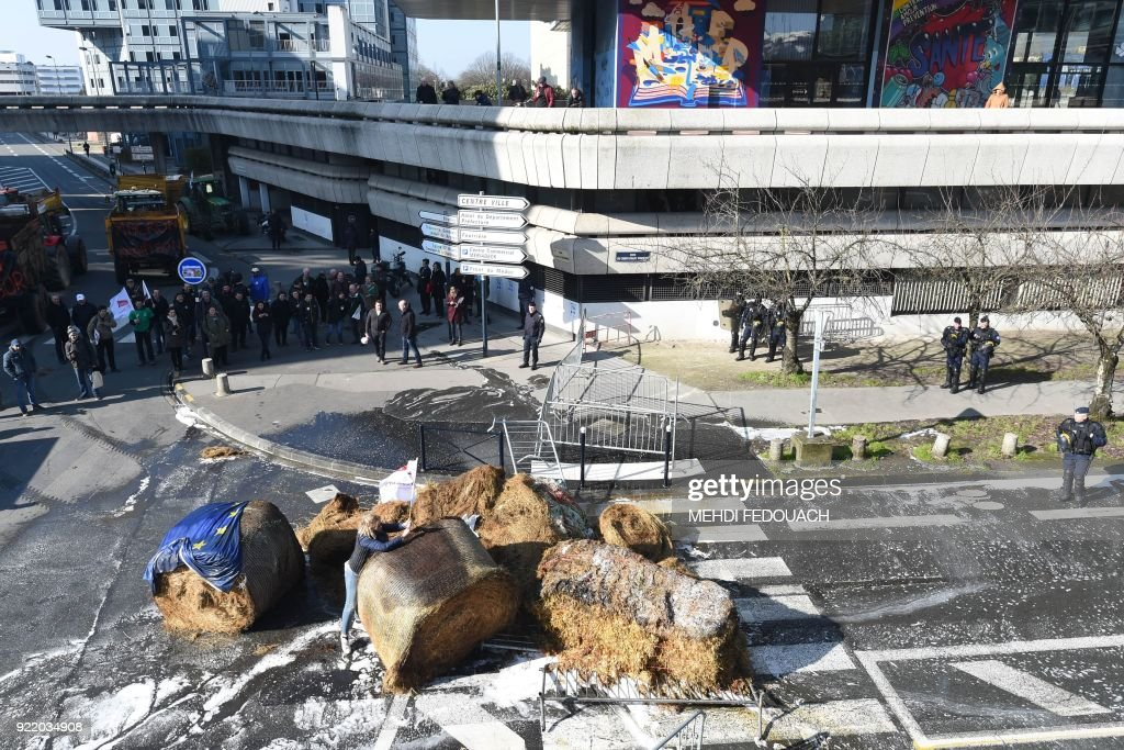 French farmers pile bundles' hay and tyres to block a traffic circle during a rally, in Bordeaux, on February 21, 2018 to protest against the negotiations between the Mercosur and the European Union on the new map of disadvantaged areas. /
