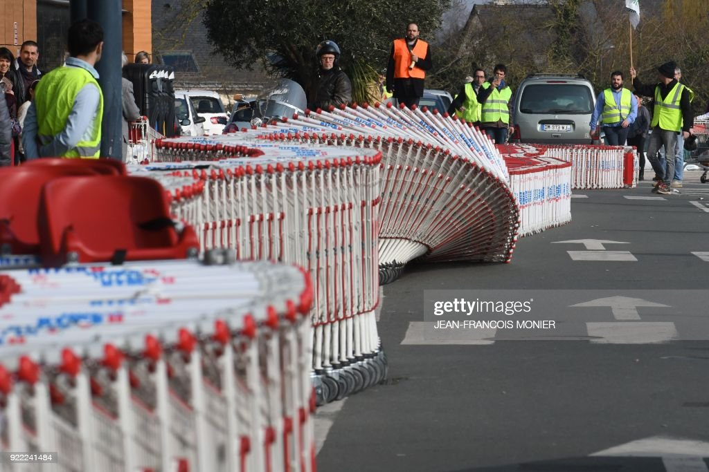 French farmers push over shopping trolleys during a demonstration against France's signing of the EU/MERCOSUR agreements between Europe and South America, outside a super market on February 21, 2018, in Angers, northwestern France. / AFP PHOTO / Jean-Francois MONIER