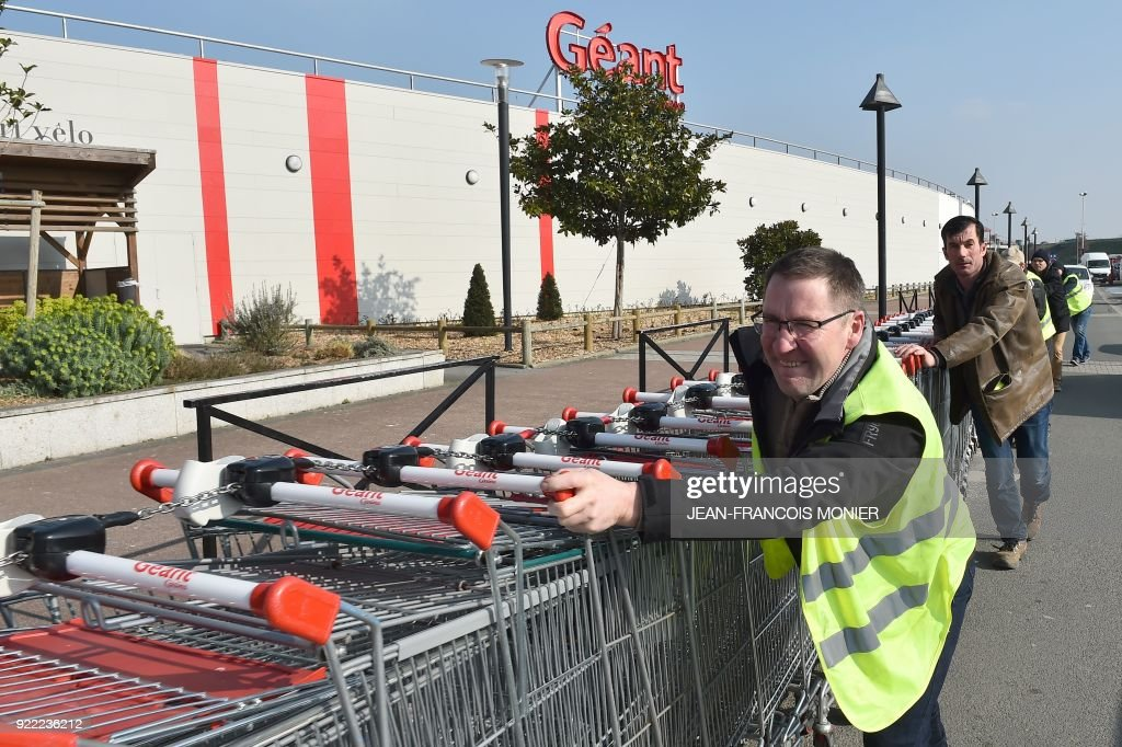 French farmers push shopping trolleys during a demonstration against France's signing of the EU/MERCOSUR agreements between Europe and South America, outside a super market on February 21, 2018, in Angers, northwestern France. /