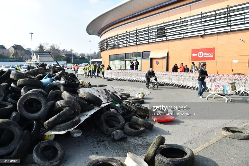 French farmers push shopping trolleys near a pile of tyres during a demonstration against France's signing of the EU/MERCOSUR agreements between Europe and South America, outside a super market on February 21, 2018, in Angers, northwestern France. /