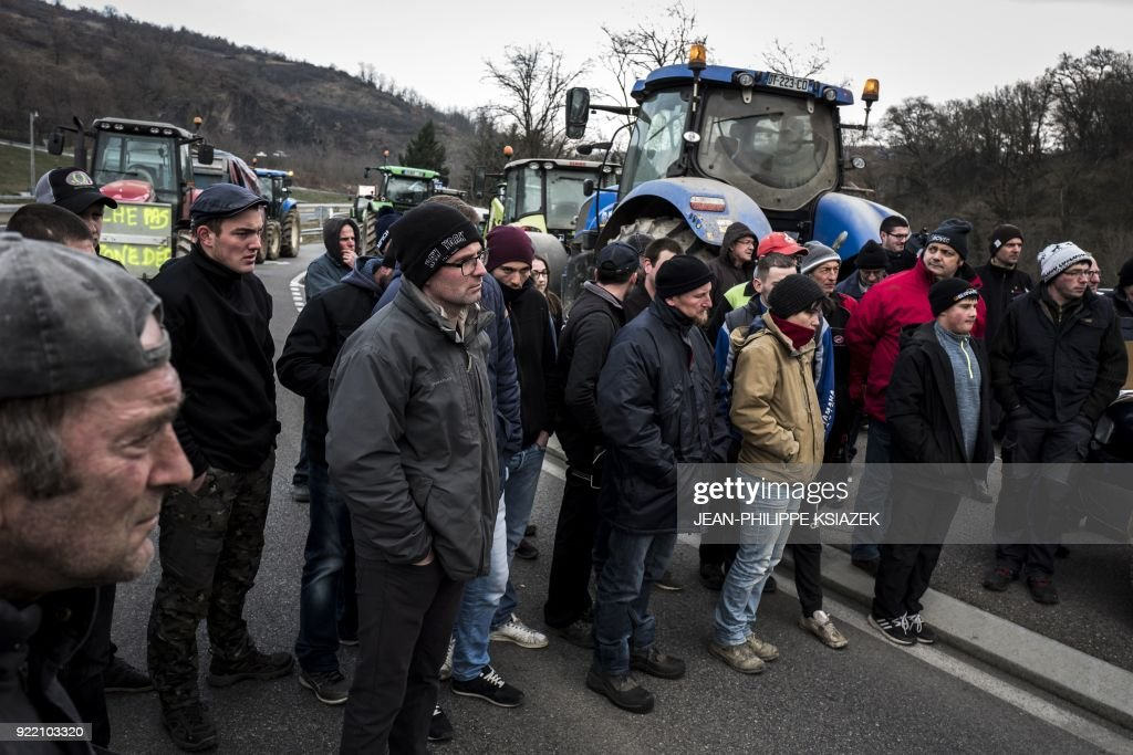 French farmers stand near their tractors as they block the A47 highway near Lyon during a demonstration on February 21, 2018 to protest against the negotiations between Mercosur and the European Union and the revision of the map of disadvantaged areas through which certain communes receive aid. Negotiators from Mercosur and the European Union are due to resume talks on February 21 after edging closer to a historic trade deal during the last round in Brussels. /