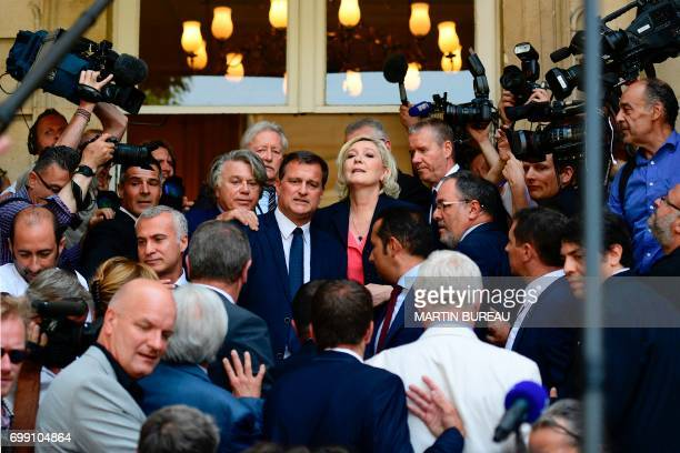 French farrigh Front National party's newly elected Members of Parliament Louis Aliot Marine Le Pen and Gilbert Collard pose as they arrive on June...