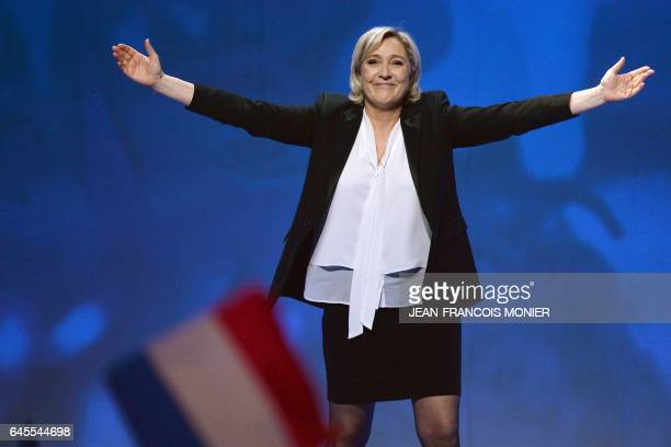 TOPSHOT French farright Front National party candidate for the presidential election Marine Le Pen waves as she arrives to speak on stage during a...