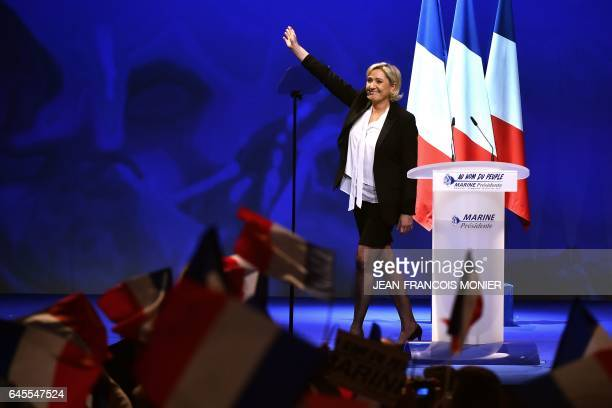 TOPSHOT French farright Front National party candidate for the presidential election Marine Le Pen acknowledges applause after speaking on stage...