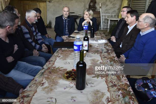TOPSHOT French farright Front National party candidate for the presidential election Marine Le Pen speaks with farmers and breeders during a visit to...