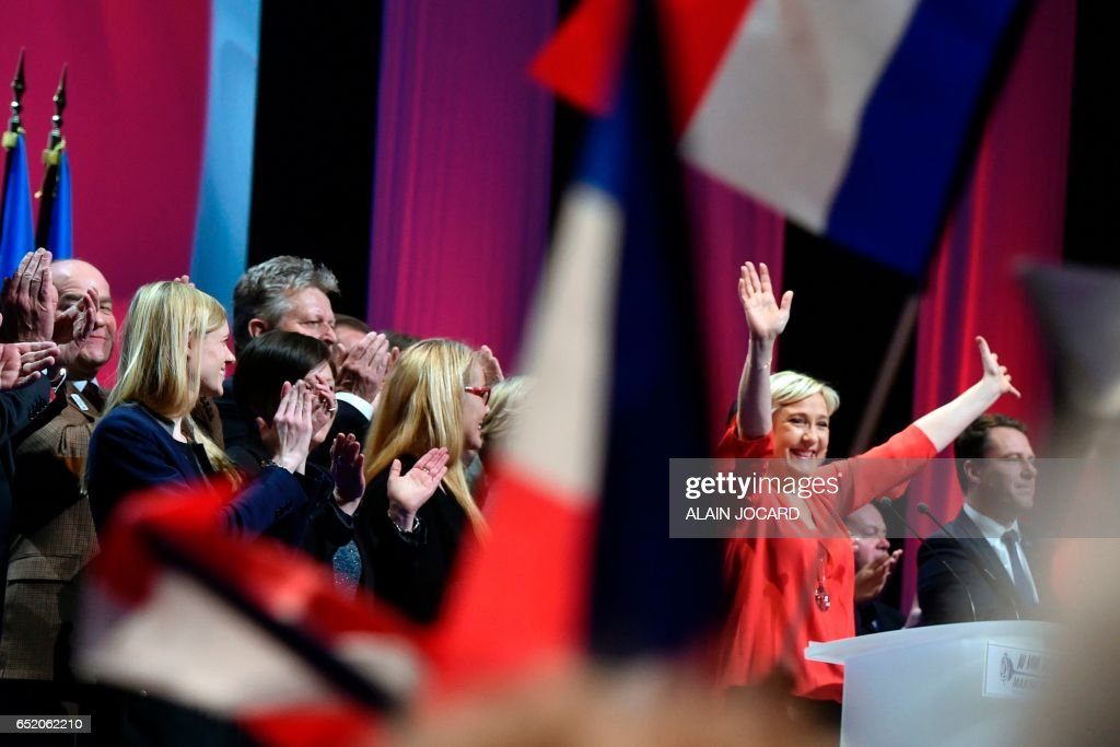 French far-right Front National (FN) party candidate for the presidential election Marine Le Pen (2nd R) reacts after delivering a speech during a campaign rally on March 11, 2017 in Deols, central France. /