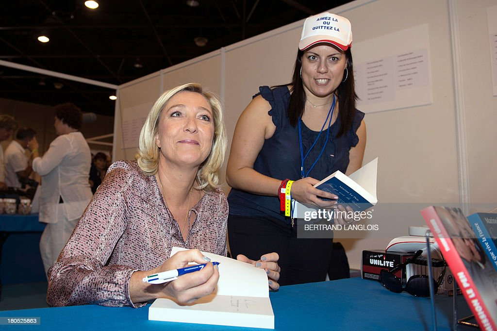 French far-right Front National (FN) party president Marine Le Pen (L) signs autographs as she attends the FN summer congress on September 14, 2013 in Marseille, southern France.
