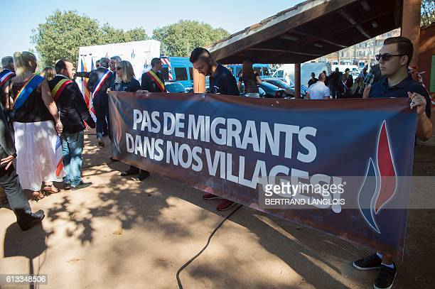 French farright Front National 's supporters hold a banner which translates as No migrants in our villages as they take part in a rally against the...