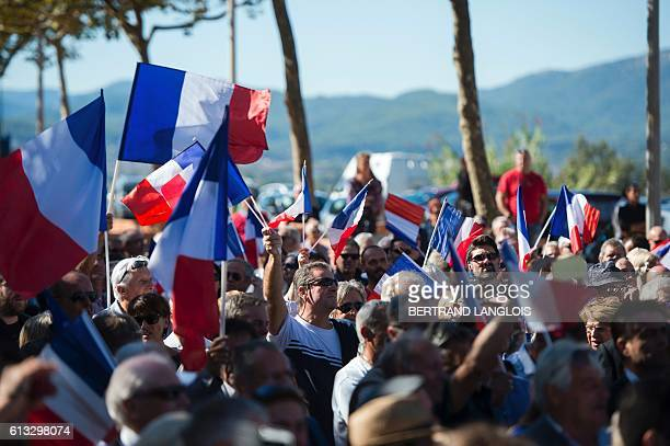 French farright Front National 's supporters wave French national flag as they take part in a rally against the possibilty of welcoming refugees in a...