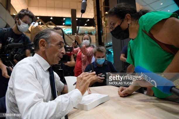 """French far-right media pundit Eric Zemmour signs autographs during the promotion launch event for his new book """"France hasn't said its last word"""" in..."""