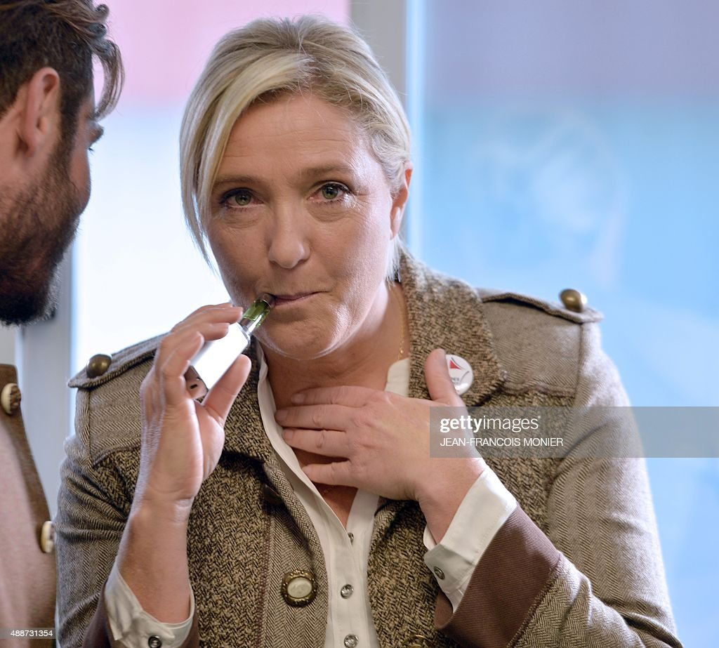 French far-right National Front (Front National, FN) party President Marine Le Pen (C), sokes an electronic cigaret prior to a press conference during a visit to the 28th International Livestock Trade Fair (SPACE, Salon international des Productions Animales) outside Rennes, northwestern France, on September 17, 2015.