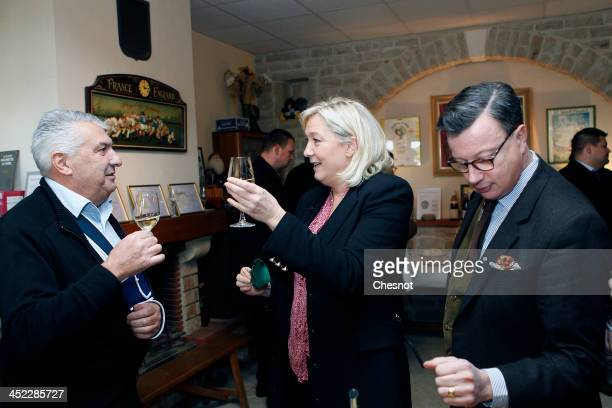 French farright National Front's Leader Marine Le Pen drinks Chablis with guests during her visit to a vineyard on November 27 2013 in Sens France