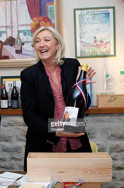 French farright National Front's leader Marine Le Pen shows a bottle of Chablis with her photograph on it during her visit to a vineyard on November...