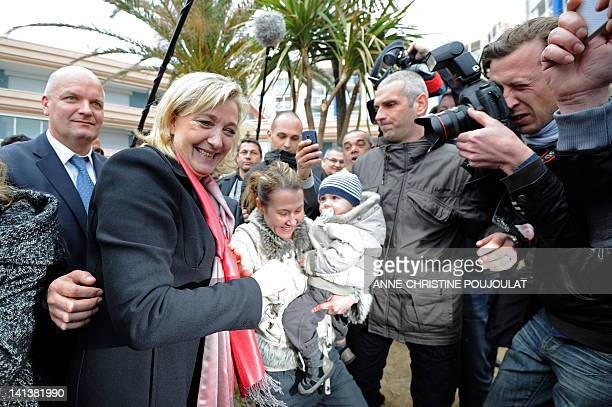 French far-right party Front national president and FN candidate for 2012 French presidential election Marine Le Pen shakes hands with wellwishers...
