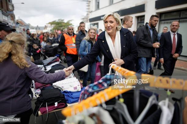 French farright political party National Front leader Marine Le Pen greets supporters as she visits the HeninBeaumont Braderie on September 10 2017...