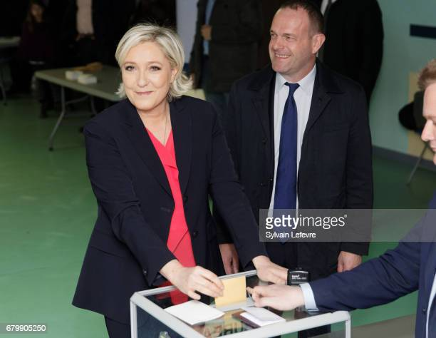 French farright presidential candidate Marine Le Pen flanked by HeninBeaumont's mayor Steve Briois casts her ballot as she votes for the 2nd round in...