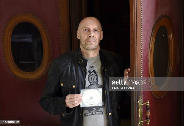French farright writer Alain Soral poses holding disc as he arrives at the Paris courthouse in Paris on March 12 for his trial for posting a picture...