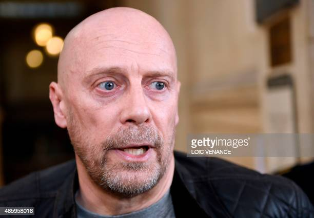 French farright writer Alain Soral speaks to journalists as he arrives at the Paris courthouse in Paris on March 12 for his trial for posting a...