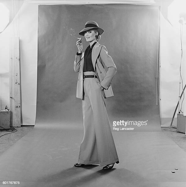 French fashion - a trouser suit by Yves Saint Laurent in stone gabardine with a double-breasted jacket, green crepe-de-chine shirt and stone felt...