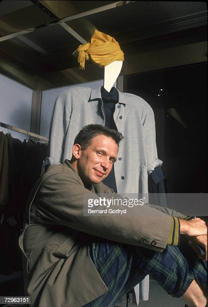 French fashion designer and television host JeanPaul Gaultier sits for a portrait next to a twodimensional mannequin New York September 1984