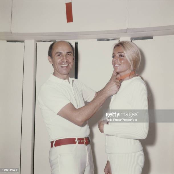 French fashion designer Andre Courreges pictured dressed all in white as he ties a bow around the next of a female fashion model in 1970