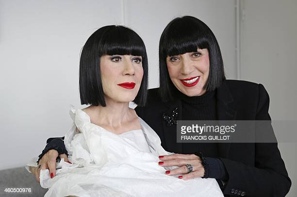 French fashion designer Chantal Thomass poses next to her wax effigy on December 10 2014 at the Grevin museum workshop five days ahead of its...