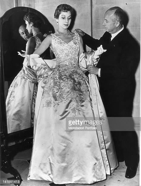 French fashion designer Christian Dior arranging one of his evening dresses. Paris, 1940s
