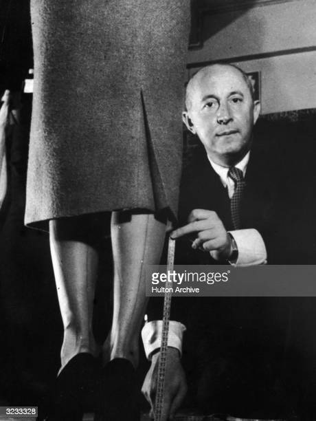 French fashion designer Christian Dior demonstrates with a tape measure and a model how he revolutionized fashion by lowering hemlines Paris France